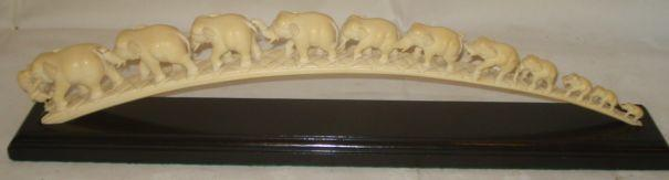 A carved ivory elephant troop, the graduated animals largest to the front being attacked by a lion, on an ebonised wooden base,43cm, minor damages.