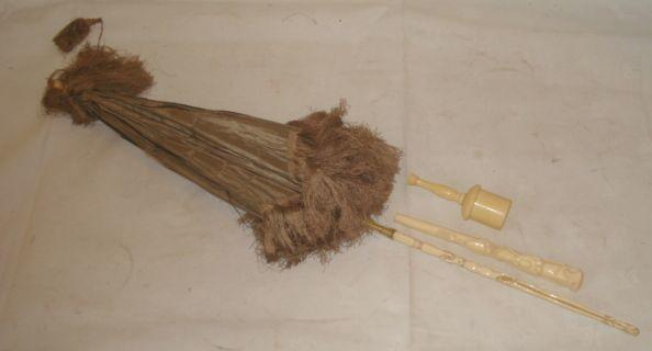 A turned ivory sectional wig powderer, circa 1820, 10.5cm, a carved ivory parasol handle decorated with flowers, leaves and cartouche, 19.5cm, and a parasol with silk tasselled shade and carved ivory handle. (3)
