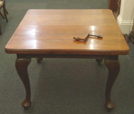 An early 20th Century walnut extending dining table, the rectangular top with extra leaf, on cabriole legs, 148 x 103cm.