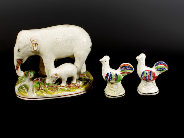 A Staffordshire elephant and calf group and a pair of Portobello-type models of cockerels, circa 1870-80