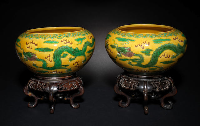 A pair of Chinese compressed circular amber glazed bowls, painted around the sides with dragons chasing flaming pearls, six character mark, 26cm and two carved hardwood stands. (4)