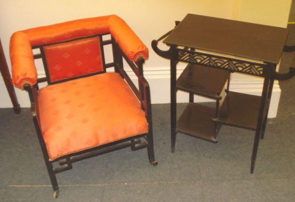 A aethetic period ebonised two tier table, with side rails over staggered shelves, 51 x 34cm, together with an ebonised frame open armchair, in the manner of Godwin. (2)