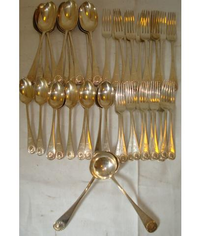 A part canteen of Victorian shell pattern flatware, comprising eleven supper forks, eleven dinner forks, two sauce ladles, and nine dessert spoons, engraved crest by Francis Higgins 1891, 89ozs.
