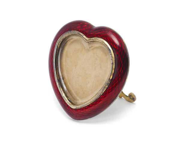 A Miniature giltmetal and red enamel miniature photgraph frame in the Faberge manner the hinged strutt bearing psuedo Russian marks,