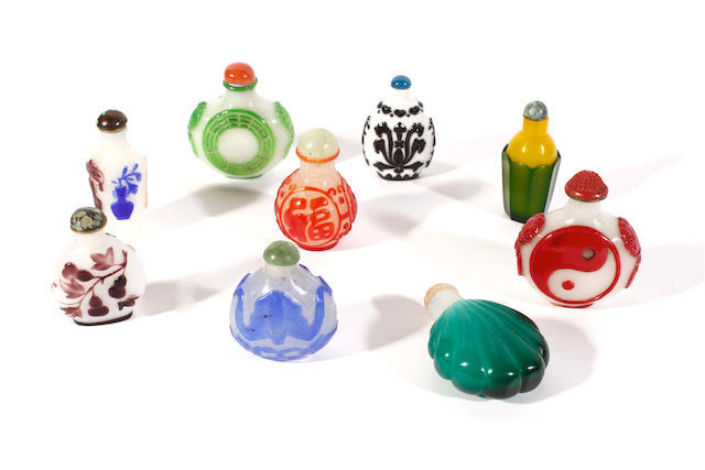 A group of nine glass overlay snuff bottles and stoppers
