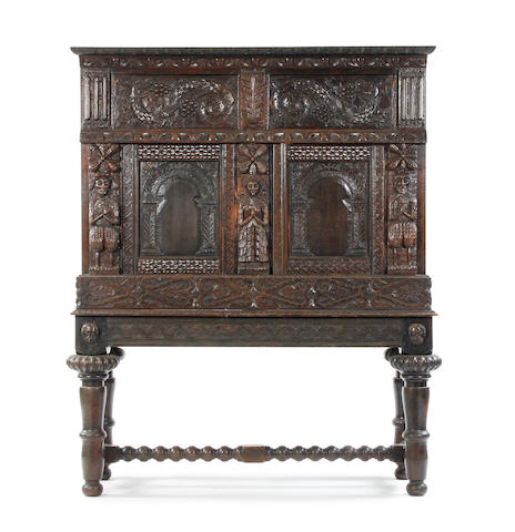 An oak cupboard on stand Constructed in the 19th century incorporating some late 16th/17th century carving