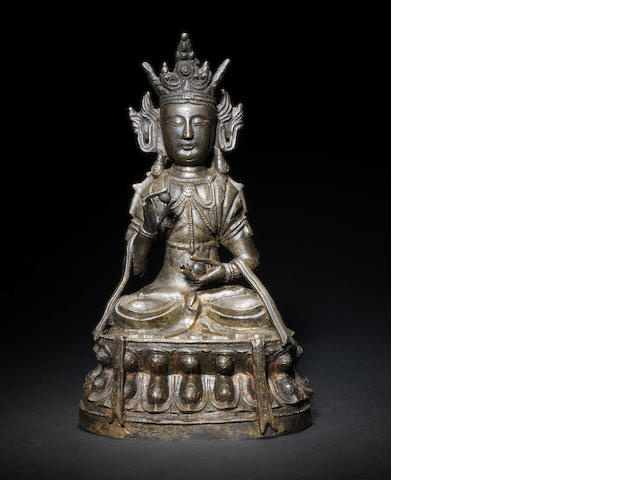 A bronzed metal figure of a Buddhistic deity, possibly Maitreya