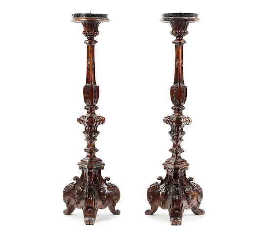 A pair of stained beech Baroque standing pricket candlesticks