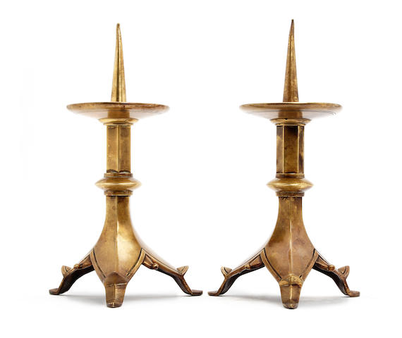 A pair of brass pricket tripod-base candlesticks, in the Gothic manner
