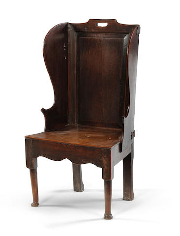 A mid 18th Century oak and elm winged hall chair