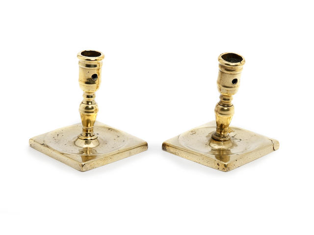 A pair of late 17th century/early 18th century square-based brass candlesticks, probably Spanish
