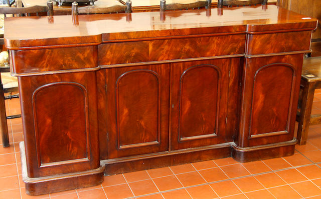 A Victorian mahogany sideboard inverted breakfront outline, with three frieze drawers and cupboards below on plinth base, 183cm wide and a Victorian gilt gesso overmantel with arched back and leaf design border, 136cm wide.