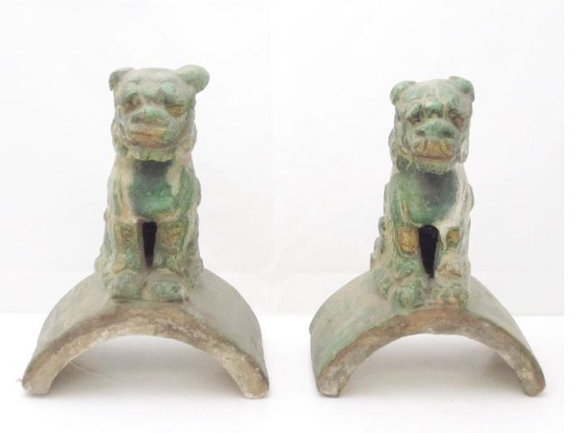 A pair of earthenware roof tile caps