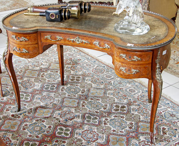 A Louis XV style kingwood gilt metal mounted kidney shape writing table, late 19th Century, the inset top within a pierced gallery, fitted with four drawers disguised as five around a kneehole, on slender cabriole legs, 122cm.