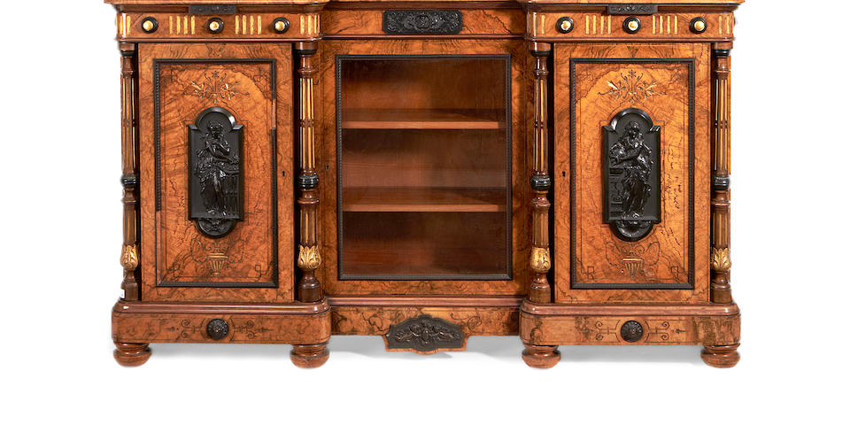 A mid Victorian ebony mounted figured walnut and parcel gilt decorated inverted breakfront cabinet
