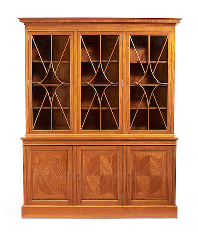 An Edwardian satinwood and rosewood crossbanded library bookcase by Maples & Co.
