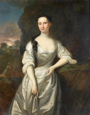 Circle of John Vanderbank (London 1694-1739) Portrait of a lady, three-quarter-length, in a white silk dress, standing in a landscape