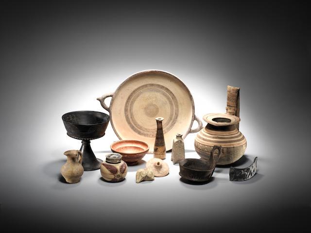 Twelve pottery vessels & objects: Cypriot chariot wheel(12), Cypriot pottery dish(15), small pottery vessel(24), Roman terra sigillata bowl(25), Etruscan bucchero ware kyathos(29), Daunian geometric decorated vessel(35), Etruscan bucchero Ware chalice(36), Corinthian aryballos(21), Etrusco-Corinthian alabastron(32), Ancient Near Eastern tripod vase(34), Bucchero Ware handle fragment(list 2/1) & an Ancient Near Eastern Astarte figure fragment(list 2/12)
