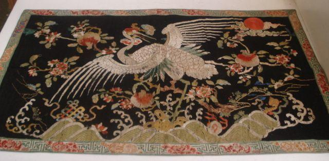 A Chinese embroidered silk panel of a crane, Qing dynasty, 19th Century, amongst flowering branches, on a black ground, 55 x 92cm, unframed.