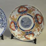 A Chinese export blue and white charger and an Imari charger, wood stands