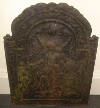 A 17th/18th Century cast iron fireback, of broken arch form, with a central winged Saint holding a shield and cross, scroll cast frame,84 x 61cm.