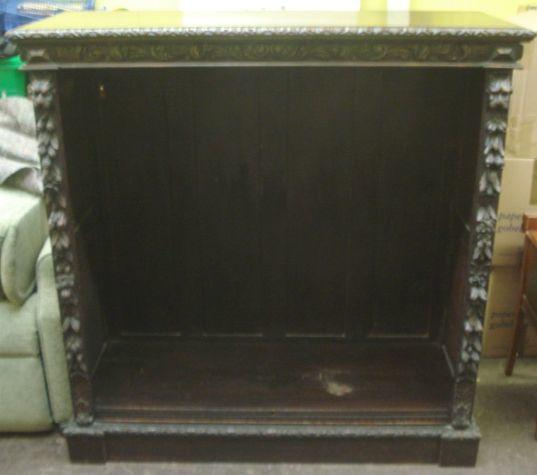 "A Victorian carved dark oak bookcase, the leaf carved frieze with fruit carved uprights flanking adjustable shelves on a plinth base, 342cm wide x 134cm deep x 140cm high, (135"" wide x 53"" deep x 55"" high)"