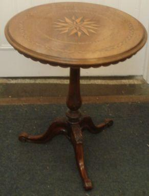 A Victorian walnut circular tilt-top table, with central shellar inlay within chevron bands and a scalloped frieze on a fielded turned column and leaf carved cabriole legs, 61cm diameter.