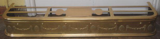 A 19th Century brass fire kerb, of bowed shape with paterea and swag decoration, the top with brass trivet bars,120 x 29cm.