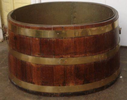 An early 20th Century brass coopered and bound circular log bin, with side carry handles and a removeable liner, 67cm diameter.