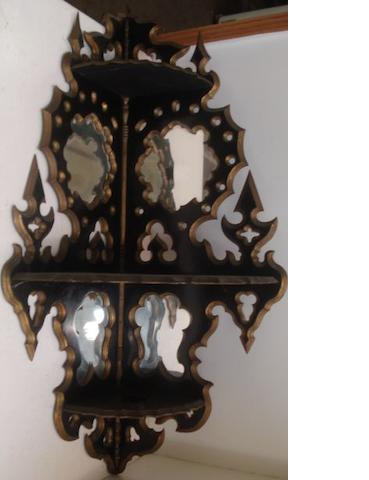 A 19th Century French ebonised and gilt corner shelf bracket, with 'Gothic' mirror back panels, 102cm.