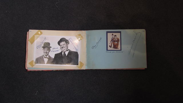 An autograph book containing two sets of Laurel and Hardy signatures,
