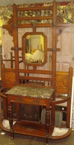 An Aesthethic period oak and ebonised hall stand, the octagonal mirror inset back with rows turnings above and below, having brass hooks, the projecting base with grey veined marble top above a drawer flanked by elliptical quarter round stick compartments, the undertier with drip trays, turned legs, 121cm.