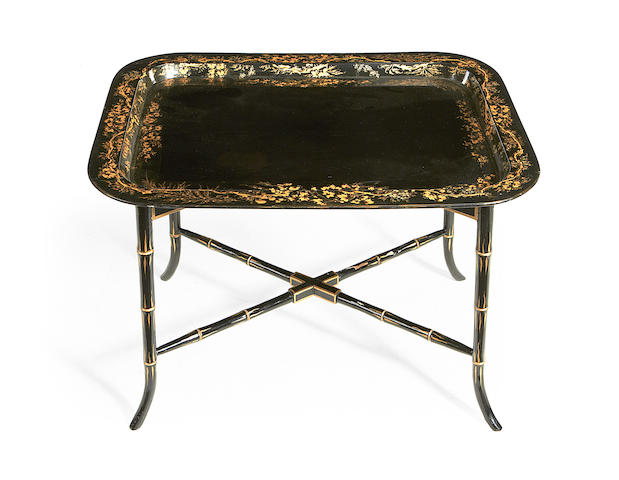 A Regency ebonised and gilt decorated papier mache tray on later simulated bamboo stand