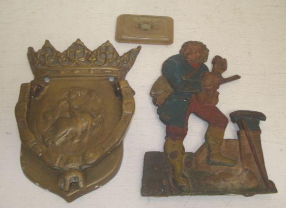 A brass door knocker,  19th Century, the shield backplate surmounted by a Crown, 21cm, a 19th Century polychrome painted cast iron figure of a travelling musician, 21.5cm, and a 19th Century horn snuff box. (3)