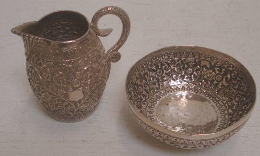 A late 19th Century Indian silver barrel shape cream jug,with snake handle, the sides heavily embossed with flowering branches and a similar sugar bowl, 8ozs. (2)