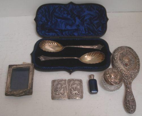 A cased pair of Victorian silver fruit serving spoons, Sheffield 1890, with gilt lined scallop shell bowls, and the following silver, a mounted easel photograph frame, heavily foliate embossed hand mirror and cut glass jar, a mounted Victorian 'Bristol blue' glass perfume bottle, and a buckle, embossed with animals beneath trees, 8ozs weighable.