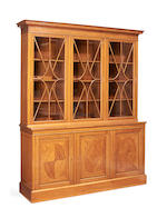 An Edwardian satinwood and rosewood crossbanded library bookcase probably by Maples & Co.