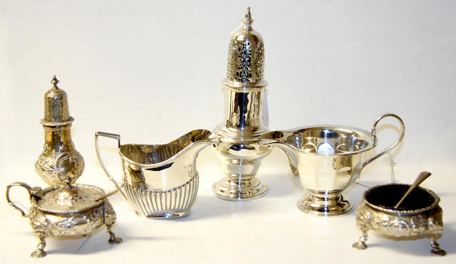 A baluster castor,Sheffield 1924, a three piece condiment set of mid-18th Century design, the circular salt and mustard with blue glass linets, on pad feet, the pepper of muffinier form 1910 and two cream jugs (6).