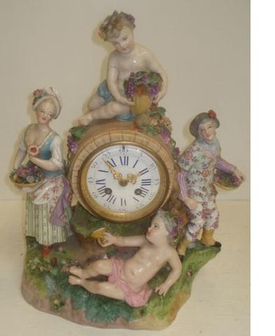 19th Century Dresden porcelain mantel clock, the case modelled as two grape harvesters and two baccante around a grape decorated barrel, key and pendulum, 41cm.