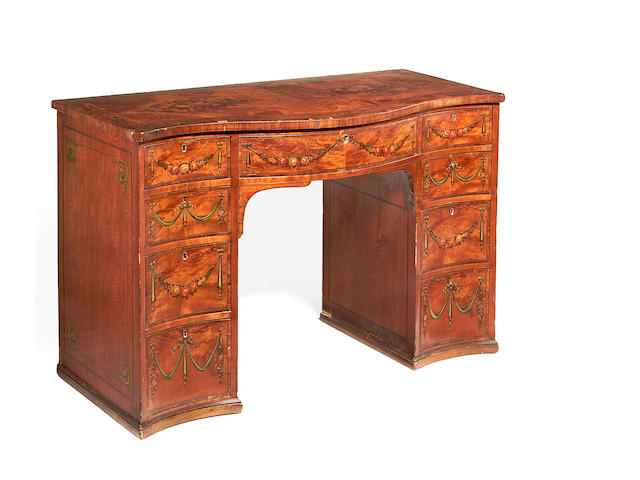 A late Victorian satinwood, rosewood crossbanded and polychrome decorated serpentine kneehole desk in the Sheraton revival style