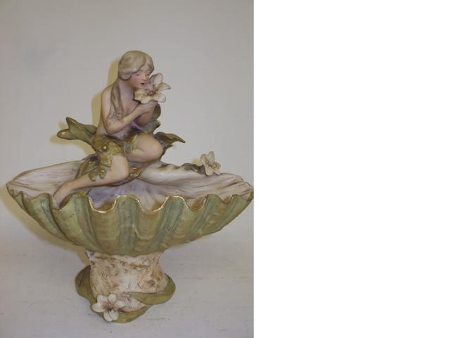 A Royal Dux figurine of a girl in a seashell