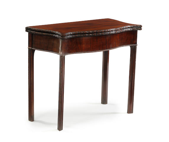 A George III-style mahogany fold-over serpentine tea table