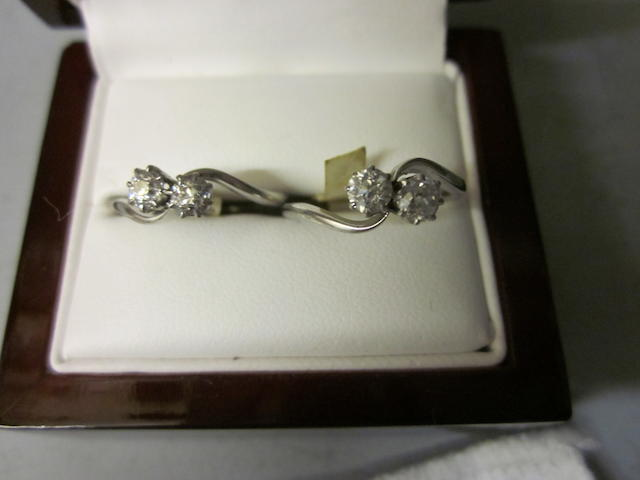 A two stone diamond crossover ring, (2)