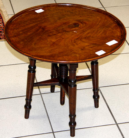 An early 19th Century circular fruitwood adjustable table