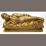 A gilded metal figure of a sleeping Buddha,