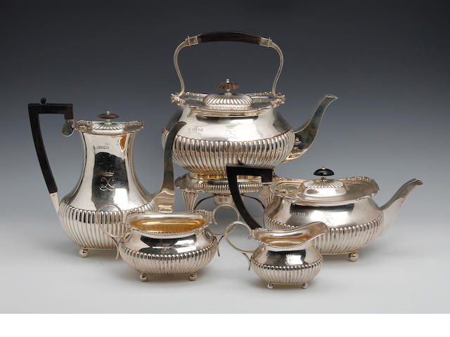 A late Victorian silver five piece tea and coffee service of half fluted form, London 1887 and 1889, in a fitted oak box.  Weight 112 ozs (3360 grams)