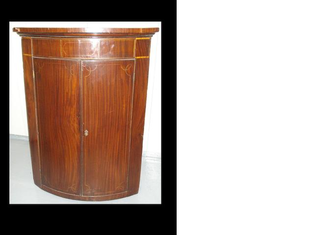 A mahogany bowfront hanging corner cupboard