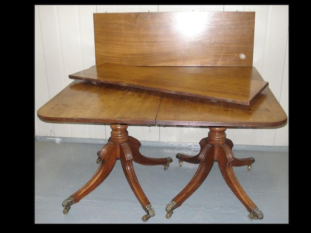 A mahogany twin pedestal dining table with two extra leaves