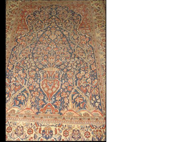 A Kirman prayer rug  with a navy ground and a mihrab covered with flowering vines and branches within similar floral borders,