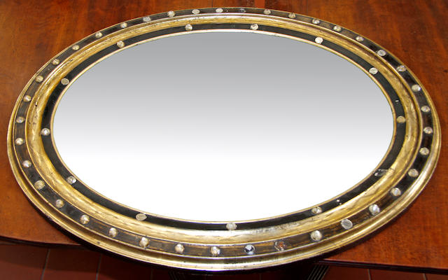 A 19th century oval Irish gilt and ebonised wall mirror